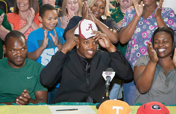 Surrounded by family and friends, Derrick Henry slips on Alabama cap during a press conference.