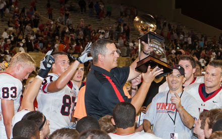 Union coach Kirk Fridrich holds up the trophy signaling a victory in the Backyard Bowl, traditionally one of the nation's biggest rivalry games.