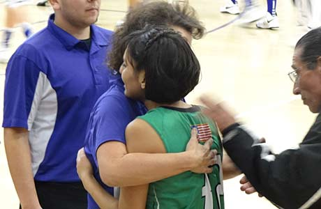 Mora's Kayla Romero receives a hug from Santa Rosa head coach Alice Velasquez on Dec. 22, just days after Romero learned that her cancer had resurfaced.